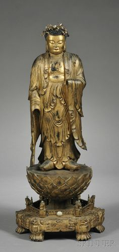 Giltwood Buddha, China, Ming dynasty (1368-1644), standing figure of Buddha atop a triple lotus throne, further set on a galleried hexagonal stand supported on paw feet, the Buddha with downcast eyes and benevolent expression, his robe falls into elegant folds, wearing a crown of thin gilt-brass leaves and jade, ht. 41