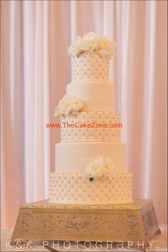 Elegant cake with gold decorations and cake stand.