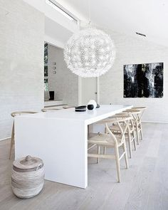 Labyrinthine mountain village architecture from all eras and regions inspired the interiors of this secluded Danish residence by NORM Architects. A sloping roof supported by pristine grey walls frames the house's dining area, with the grand centerpiece being the stunning pendant and custom Corian table that shrouds the space in a sea of relaxing neutrals. #architecture #interiors #design #interiordesign #denmark #house @normarchitects... - Interior Design Ideas, Interior Decor and Designs…