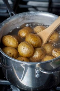 A pot of boiling water with boiled salt potatoes cooking inside.