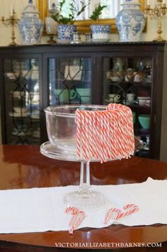Make a candy cane centerpiece out of a cake plate. Fill it with cloved oranges or glass ornaments.