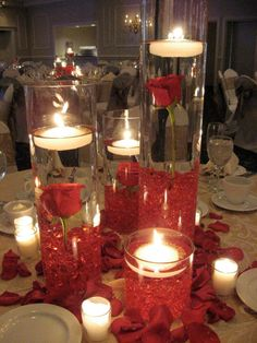 Gorgeous, long stem red roses fully immersed in water with floating tea lights. Another stunning centerpiece created by our in-house floral designer! See more at facebook.com/flowersbythewestwood #candles #wedding #centerpiece #roses