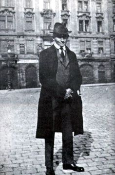 Franz Kafka in front of his family's apartment at the Oppelt House in Prague.(1922)