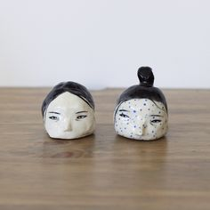 "Hand-built two floating heads. One with blue dots, the other is simple with black details. Sealed with clear glaze.Comes with a set of two. Each piece is a unique object.1 : Appx. 1 1/2"" x 1 3/4"" x 1 3/4""2 : Appx. 1 1/4"" x 1 1/2"" x 1 1/4"""