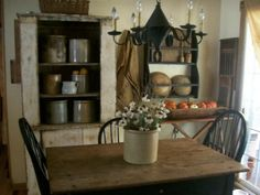 Primitive Dining...table & chairs...old cupboard with crocks & bowl shelf on the wall.
