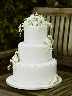 White 3-tiered, piped cake with ranunculus, rose and lily of the valley sugar flowers