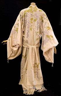 Kimono-style tea gown, c.1905. Made from pale peach silk crepe, the lightweight kimono is exquisitely hand embroidered with trailing vines of wisteria in shades of lavender and green.