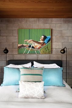 Blue pillows on white bed with beautiful artwork against exposed cement brick wall and wood ceiling