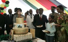 Dictator Robert Mugabe, 89, celebrates with his wife Grace, right, as they have a slice from the four-tier cake at the party in Harare, Zimbabwe