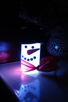 Light up snowman made from a Crystal Light container and a string of battery-operated LED lights from the Dollar Tree