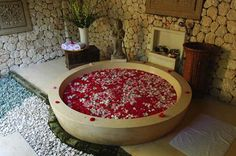 Elegant-bathroom-with-marble-bath-tub-stone- walls-roses-in-water-and ...
