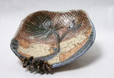 This ceramic pottery bowl features a pine branch, birch bark and a unique ceramic pine cone attached to the edge. The handmade stoneware bowl was inspired by the northwoods of Wisconsin where I live. I use a combination of handmade stamps, natural materials and drawings to achieve the pine branch arrangement on the inside of this dish.