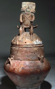 Huge Rio Magdalena Pottery Urn - Ex-Stanley Marcus. Pottery lidded jar, used to store food and water, as well as interment of the dead. Bulbous base decorated with 4 applied frogs, eyes and top of head with added shell beads - some remaining, body decorated with cross-hatched designs in deep relief. The lid is adorned with a seated male figure, hands to his knees. He sits atop a 4-legged stool made from the underside of a large turtle. This and more ancient art for sale on the…