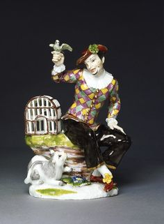 Harlequin with a Bird Cage, 1743 | Modeled by the famed Johann Joachim Kändler (1706-1775) for the Meissen Porcelain Factory in Germany, this figure of Harlequin is crafted of hard-paste porcelain.  It is depicted seated on a grass-topped rock upon which a bird cage is resting.  In his hand, he holds a green bird.  At his feet is a crouching cat.  Such figures were made, in the Eighteenth Century, to adorn the dining tables of luxurious households during the dessert course.