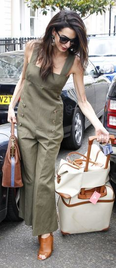Amal Clooney accessorized her Sonia Rykiel khaki-colored jumpsuit with gemstone drop earrings, a LaLa Queen striped bag, and black sunglasses. She completed her outfit with tan slingback mules and matched her look with her neutral Bric's suitcases.