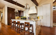 This elegant kitchen features a wide variety of wood tones and an expansive marble kitchen island, where the marble countertop extends on either side down to the hardwood flooring. The most stunning feature of this kitchen are the enormous wooden beams on the ceiling. One of the marks of luxury is architectural detail.