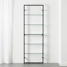 Shop Tesso Black Bookcase. Five polished clear glass shelves niched in sleek black scale the wall to dramatic heights. Designed by Mark Daniel of Slate Design, modern étagère reflects light, looks light—but powdercoated metal tube frame wallmounts super sturdy.