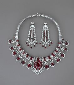 Cartier, Ruby and diamond necklace and earrings. The central element of the necklace detaches for wear as a clip brooch. Maker's marks. Contained in original fitted green leather Cartier case, with standard Cartier stamp in gilt lettering inside the lid . Made in London -1940-1950 (circa, earrings)1954 (necklace)