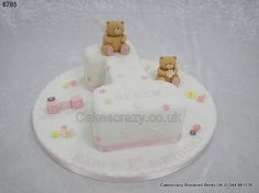 Number one first birthday cake in white with simple stars and flower decoration and finished with two forever friends handmade models http://www.cakescrazy.co.uk/details/forever-friends-bears-number-1-cake-8785.html