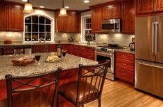 Venetian Gold granite countertops. Think I'll got with cabinets that have a bit of red in them like these do.