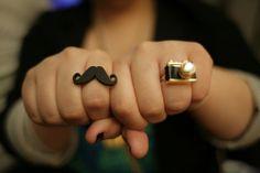 I wear moustache. He wears camera.