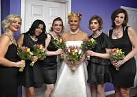 Black bridesmaid dresses with bright, colorful bouquets.