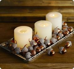 Fall/Thanksgiving decor- candles in a tray with acorns (could be real or chic fake ones as shown).  Would be a great low lying centerpiece at a fall wedding, too.