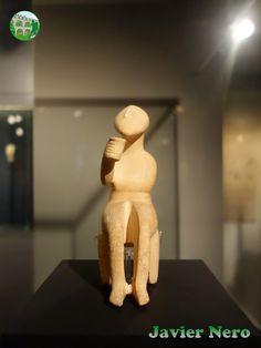 La cabeza, almendrada, se encuentra casi perpendicular al cuello cilíndrico. El brazo izquierdo se dobla por el codo y el antebrazo se coloca sobre el abdomen. El brazo derecho extendido, con el codo ligeramente, ofrece un pequeño portador. La mano extendida es una característica extremadamente rara en los trabajos de las Cícladas. Arte Cicládico antiguo período II. Grecia. Hombre con un vidrio. Estilo canónica. Fase de Syros (2800-2300 a.C.). Museo del Arte Cicládico, Atenas.