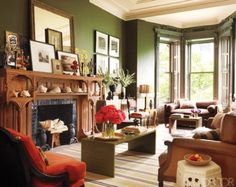 A tomato-red armchair makes a bright statement against olive green walls and earthy accents. The mix of styles — a traditional leather couch, a modern green coffee table, and an eclectic mix of knick knacks — boost the room's bold personality.