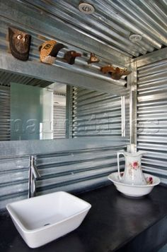 Bathroom with galvanized sheets a rectangular mirror and shower screen