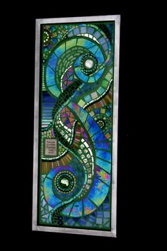 """<p>SOLD- A similar piece can be custom ordered.</p> <p>This unique mosaic is made of intertwining of iridescent glass with a 1"""" steel frame and measures 24"""" x 12"""". It contains a small metal plaque with the quote """" A journey of a thousand miles begins with a single step.""""</p>"""