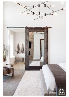 Love this sliding barn door mirror in a white bedroom window with brown accents. Would be great for a farmhouse master bedroom.