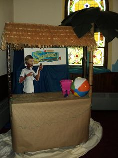 Tiki hut for island/ocean theme using a gardening table.  Attach 2x4s for braces.  Make a triangular roof from cardboard and attach grass skirts from dollar store.  Wrap the table in craft paper and top with fishing nets, beach ball, and pail.