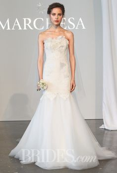 Brides.com: Marchesa - Spring 2015. Strapless silk wool mermaid wedding dress with corded lace applique details, a tulle skirt, and 3D lace rose brooch, Marchesa