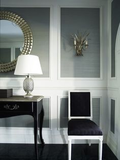Architectural molding with gray painted inset panels, black upholstered chair.