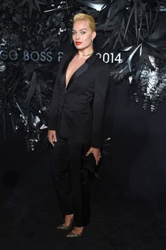 Margot Robbie working a mannish style at the Hugo Boss Prize 2014.  Wearing a Hugo Boss suit with satin lapels, slicked back hair (circa Brigitte Nielsen) and a bold orange lip.