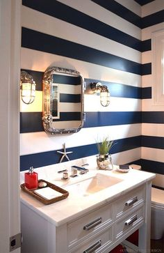 Cottage powder room boasts white and navy striped walls which is a backdrop top a nautical riveted mirror illuminated by marine cage sconces over white single washstand accented with polished nickel hardware topped with Italian marble alongside beachy accents.
