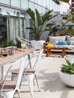 Últimos días de verano. Terraza moderna con grandes maceteros y plantas y elementos industriales en un edificio en Palermo.