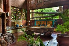 The wall color, floors, wall of colored glass, built in seating. This space is lovely. Cob Building, Building A House, Adobe Haus, Earthship Home, Earthship Design, Natural Homes, Built In Seating, Earth Homes, Natural Building