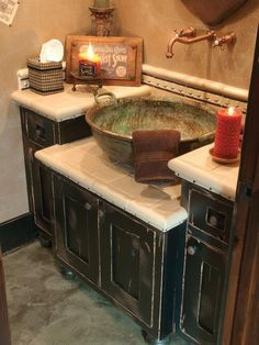 Several cupboards slid together, distressed and tiled to match provide an excellent old world-inspired vanity base for this huge old world-inspired bowl sink.