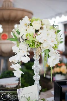 Tall crystal vase with white & green orchids
