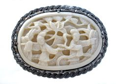 Vintage Faux Ivory - This is a Chinese Export sterling silver brooch with hand carved bone. It depicts a scene of a man and a woman turning away from each other. This pin measures 2.25 inches by 1.63