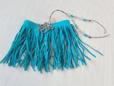 Blue faux suede upper arm bracelet with fringes. It has a lovely silver colored octopus pendant.