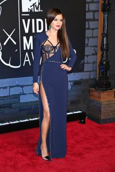 Selena Gomez looked undeniably sexy in this navy, floor length Versace gown. Her dress featured long sleeves, studded embellishments, a black sheer lace bustier, and a thigh-high slit that was jaw dropping. She looked flawless accenting her lips and nails in deep red color with a dramatic cat eye to glam up the look. Loved everything about her look!