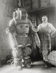 Chester E. Macduffee next to his newly patented, 250 kilo diving suit. 1911.