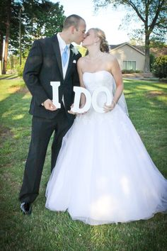 "Bride and Groom holding 'I Do"" letters"