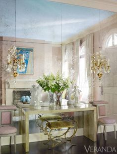 The lavish fun begins just beyond the front door, where a not-so-big great room had to contain a foyer as well as living and dining areas. Sommers gave the entry wall impact by cladding it in antiqued mirror panels and mounting Meredith's grandmother's Maison Baguès crystal sconces over a seam, with a goatskin-sheathed console table below.<br /><br /><em><strong>Vintage chairs, Grand Mere, in Manuel Canovas fabric. Antique Baguès sconces.</strong></em>