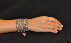 Nataly Noama Shining Star Gray Leather Bracelet: This gray African leather bracelet is embedded with delicately-placed Swarovski crystals. It's feature a silver-coated star that is also embellished with Swarovski crystals, and the bracelet can wrap around your wrist up to 4 times.