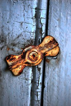 A rusted latch on an old storm window. {Remember when the weather would turn cold and the mornings had a snap in them, we would take off the screens, wash them, and then put on the storm windows. Miss those days... truly. }