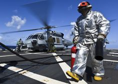 "PACIFIC OCEAN (June 29, 2016) Damage Controlman 3rd Class Erik Michel, assigned to the Arleigh Burke-class guided-missile destroyer USS Shoup (DDG 86), walks to a safe area on the flight deck after securing from refueling an MH-60R Sea Hawk helicopter attached to the ""Magicians"" of Helicopter Maritime Strike Squadron (HSM) 35 as part of flight operations, during Rim of the Pacific 2016. (Mass Comm Spec 2nd Class Holly L. Herline)"